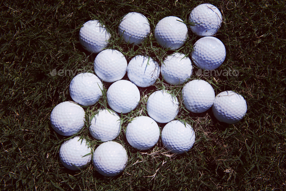 top view flat lay of golf balls with driver on grass background