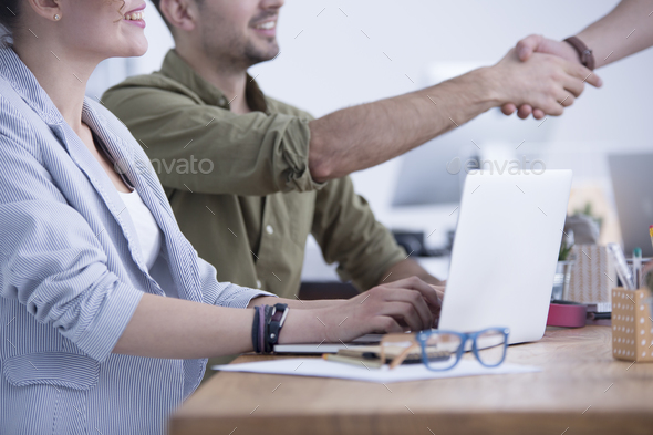 Close-up on a young businesswoman by a laptop and her blurred colleague sitting beside shaking hands with a candidate after a job interview